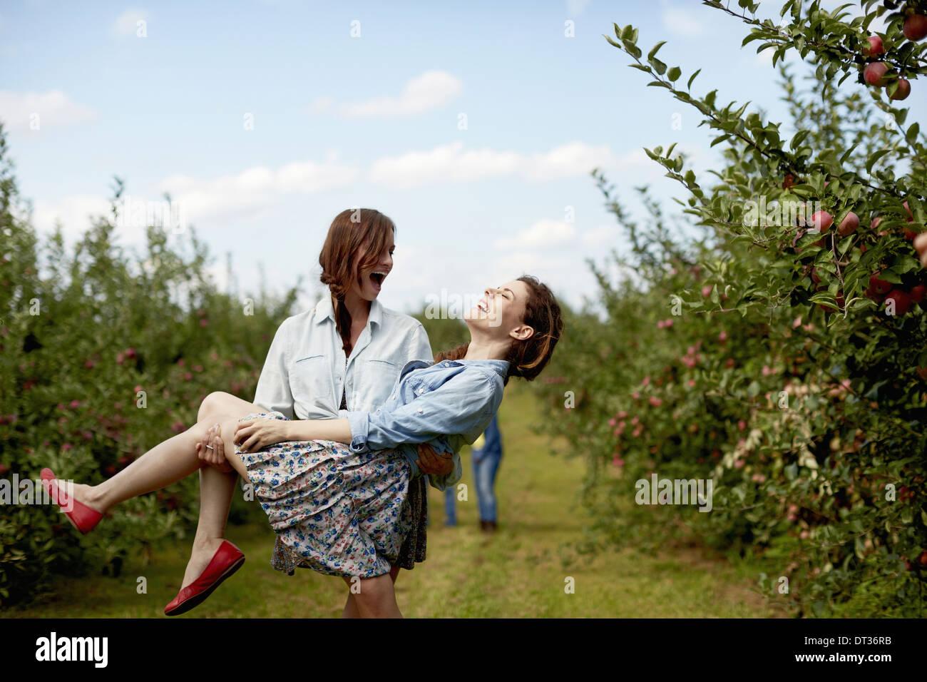 Reihen der Obstbäume in eine Bio-Obstgarten zwei junge Frauen, die eine mit dem anderen lachen Stockbild