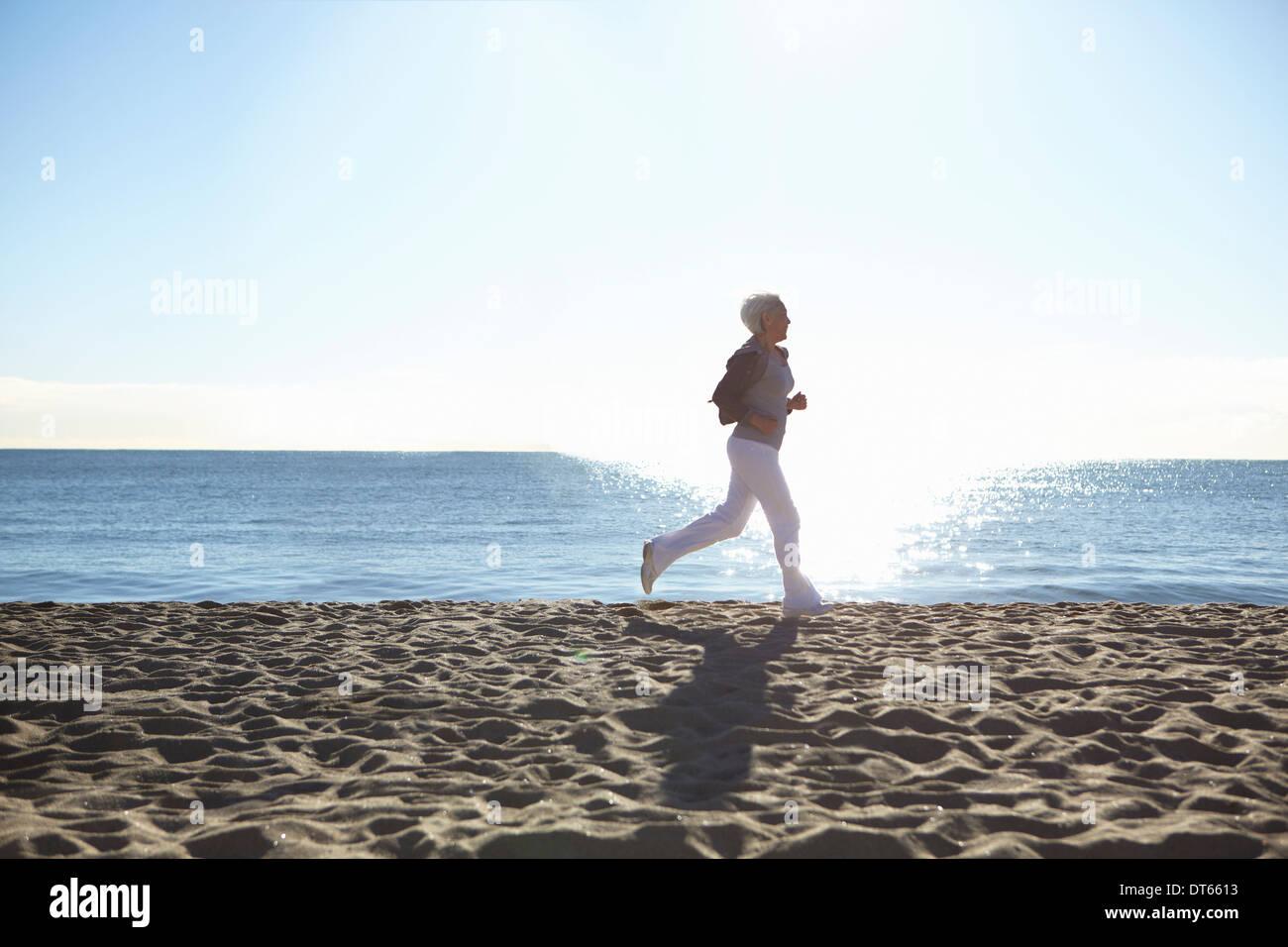 Reife Frau, Joggen am Strand Stockbild