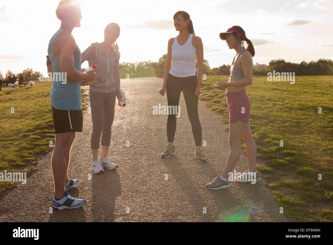 Personal Trainer mit Gruppe von Clients, die Vorbereitung laufen Stockbild