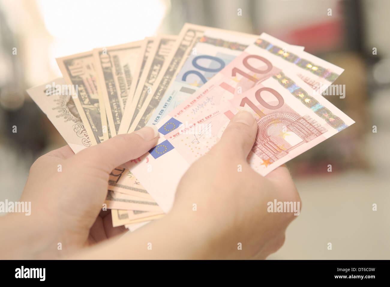 Weibliche Hände halten amerikanischen, britischen und europäischen Banknoten Stockbild
