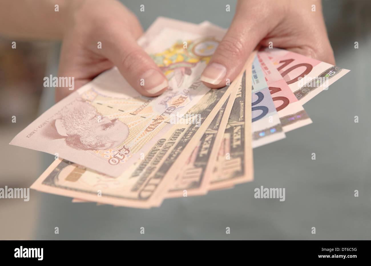 Weibliche Hände halten amerikanischen, britischen und europäischen Währung Stockbild