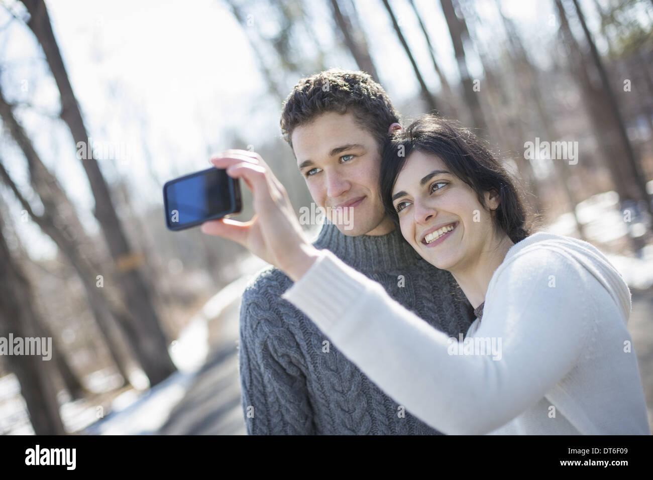 Ein paar im Freien an einem verschneiten Tag. Frau mit einem Kamera-Handy fotografieren auf Armlänge. Stockbild