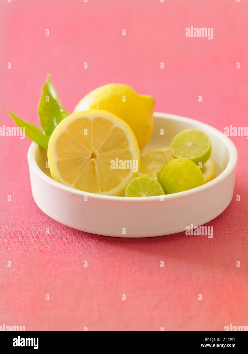 Eine zeitgenössische weiße Schüssel mit Zitronen und Limetten auf rosa Stoff Hintergrund. Stockbild