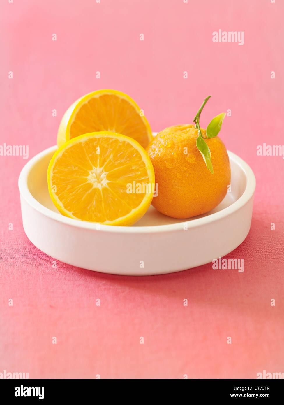 Eine weiße Schüssel mit Orangen ganze und geschnittene auf rosa Stoff Hintergrund. Stockbild
