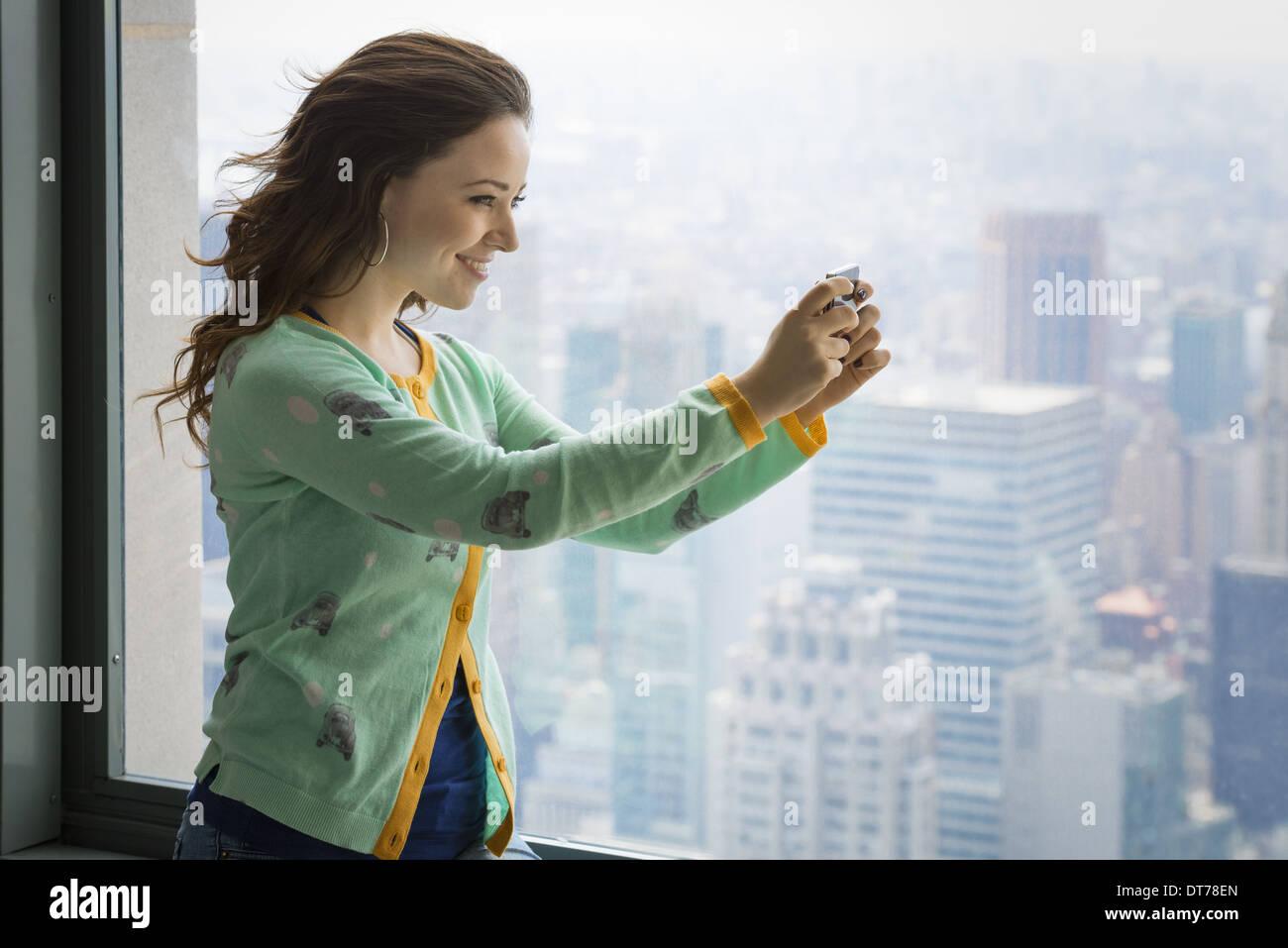 Urbaner Lifestyle. Eine junge Frau, die mit ihrer Kamera, um ein Bild von einer Aussichtsplattform über die Stockbild