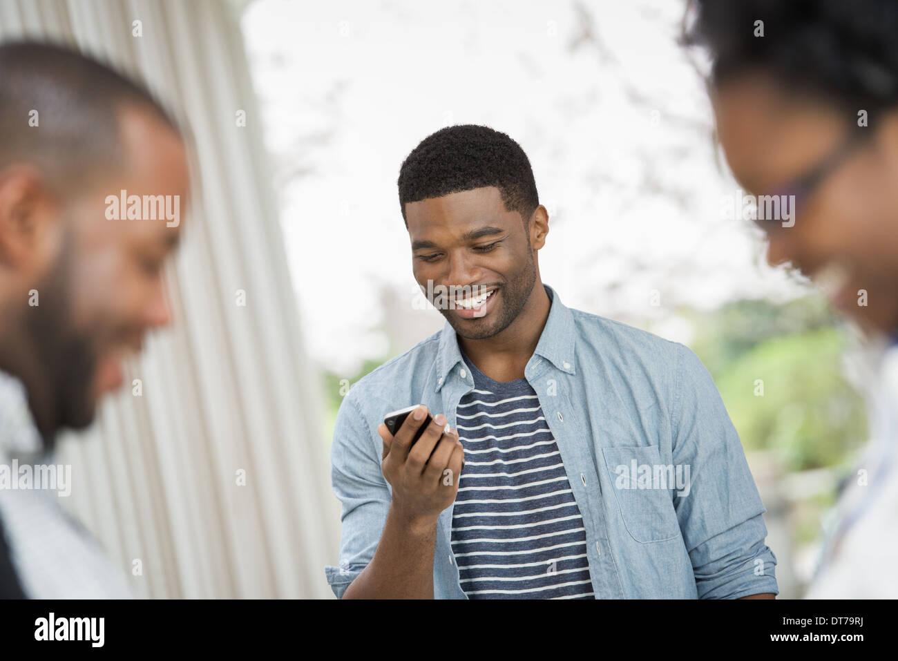 Ein junger Mann überprüft seine Telefon hinter ein paar im Vordergrund. Stockbild