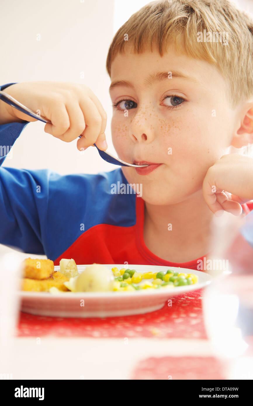 Young Boy Essen Fischstäbchen und Gemüse Stockbild