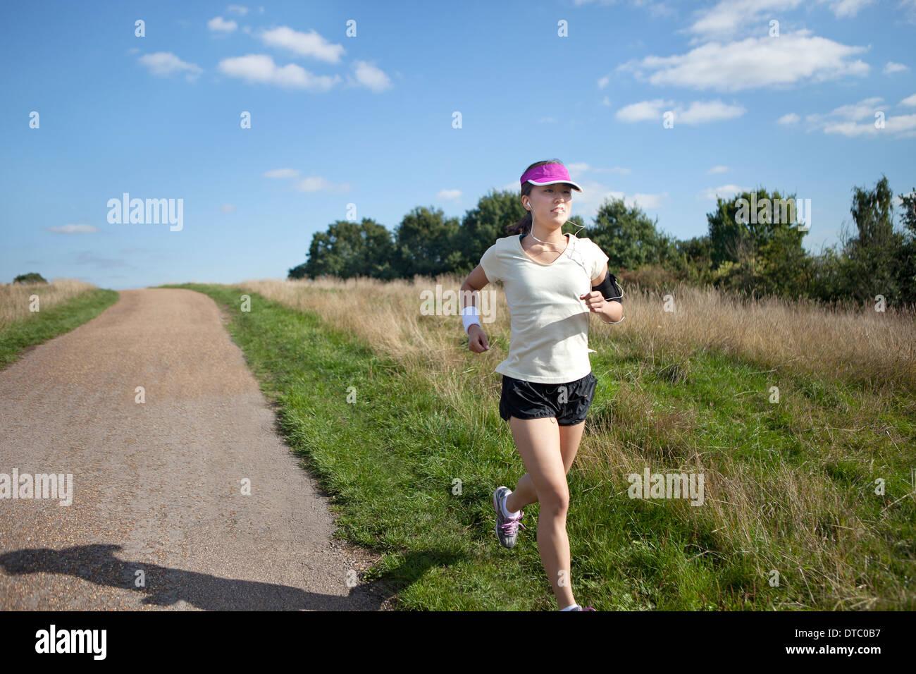 Junge weibliche Läufer läuft neben Feldweg Stockbild