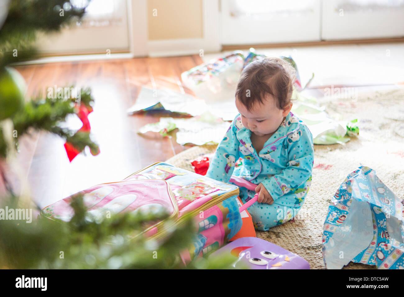 Babymädchen öffnen Weihnachtsgeschenke Stockbild