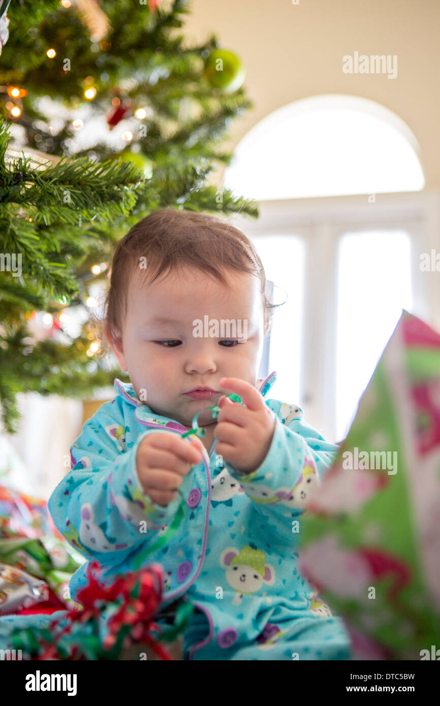 Babymädchen öffnen Weihnachten präsentiert ihr erstes Weihnachten Stockbild