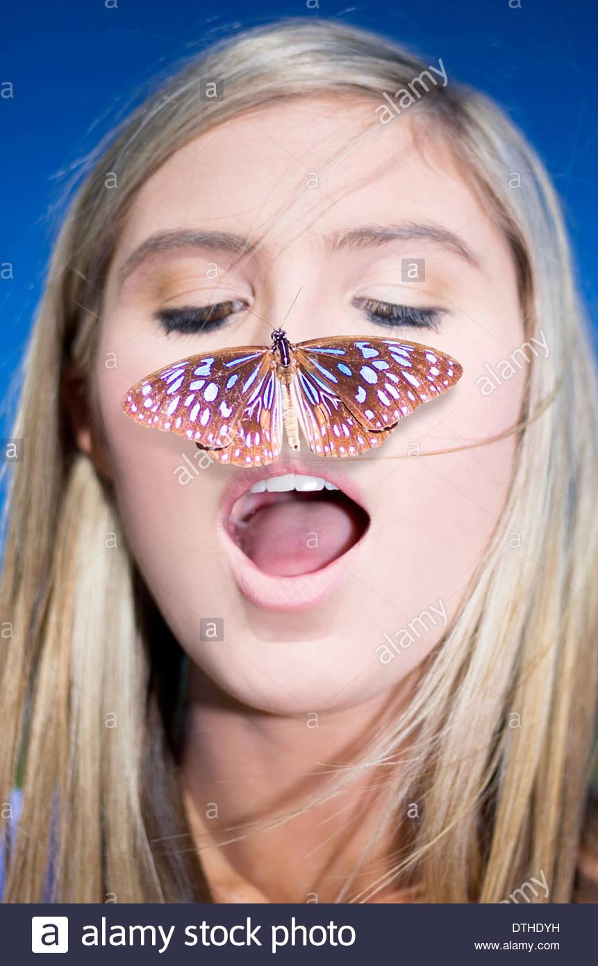 Natur-Verbindung-Konzept zeigt einen Kopfschuss eine attraktive blonde Frau mit einem Schmetterling auf der Nase Stockbild