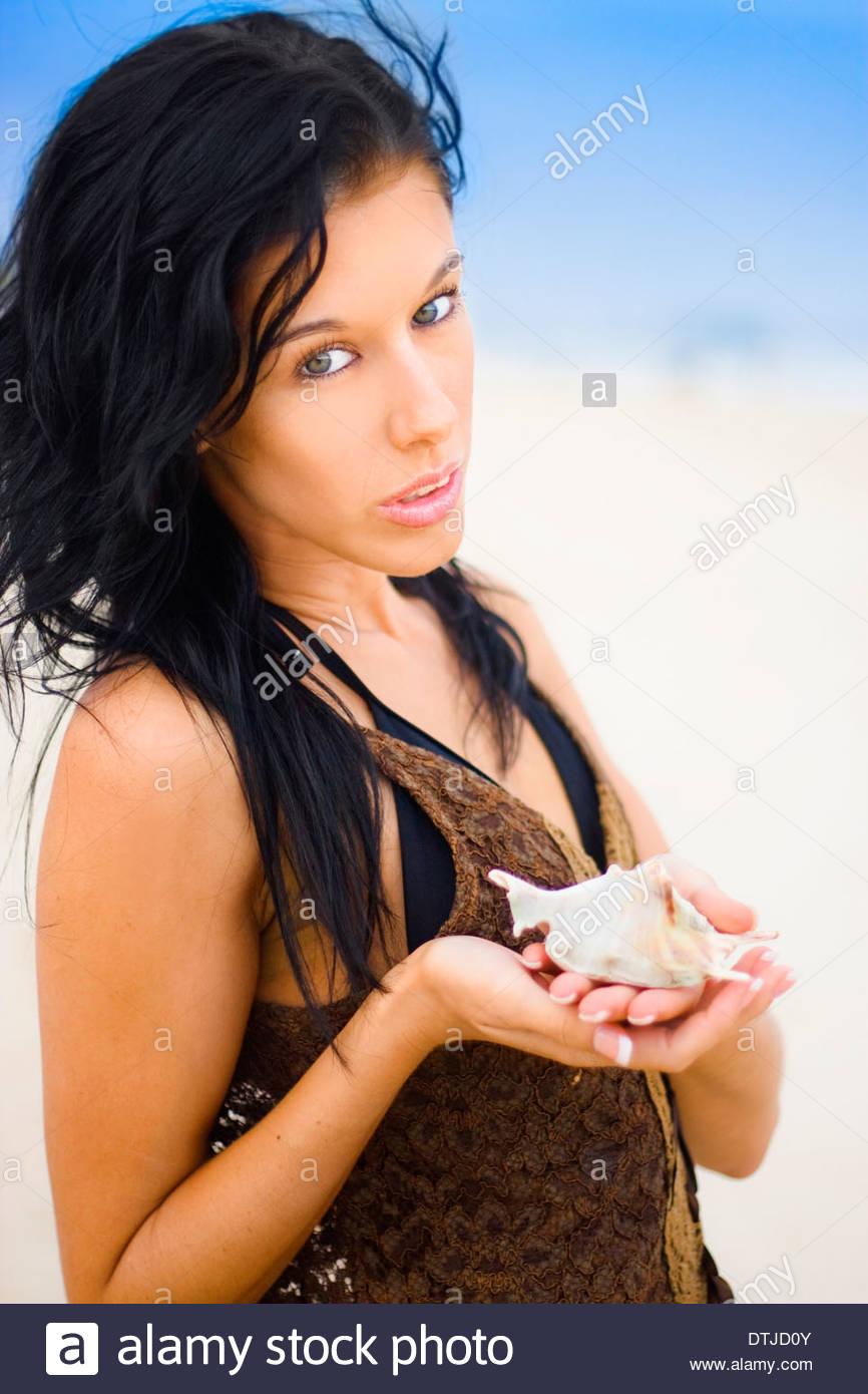 Hübsche junge Frau Seashell mit Ausdruck der Pflege halten, als ob ihre Umwelt Sorge für die Erhaltung Stockbild
