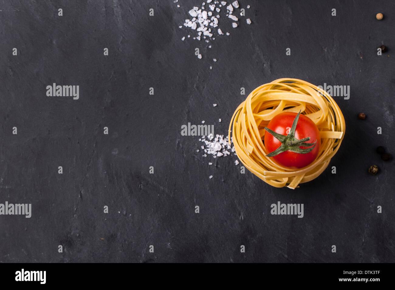 Draufsicht auf trockene Pasta und frischen Kirschtomaten, serviert mit Meersalz auf grauem Schiefer dunkel Stockbild