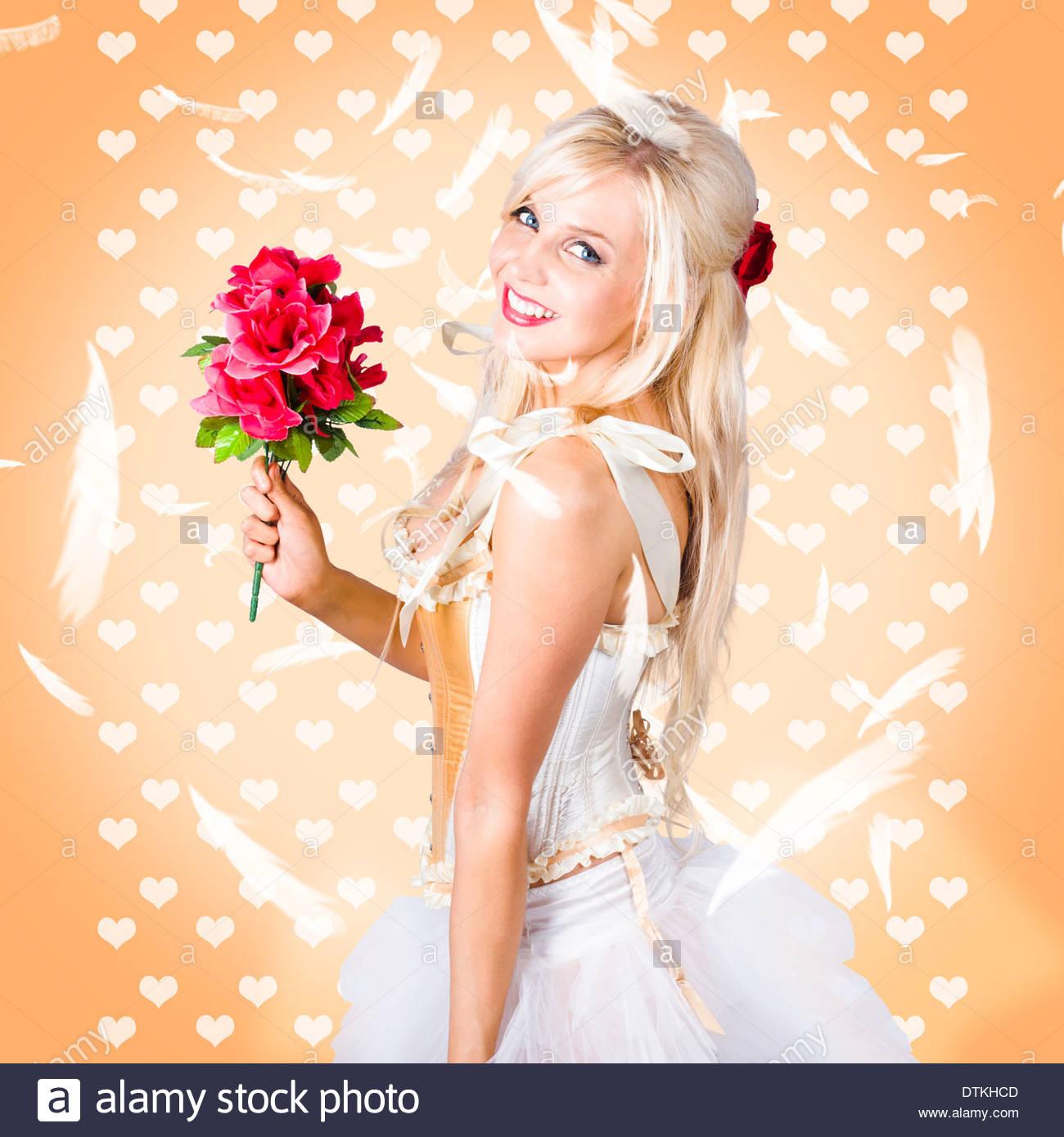Zarte junge Frau Blumenstrauß beim feiern Valentinstag mit fallenden Federn halten Stockbild