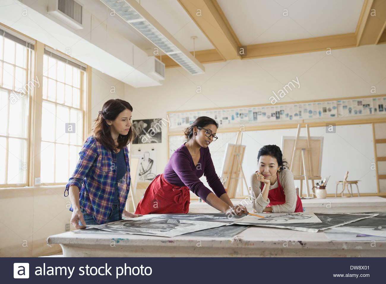 Studierende, die prüfen Kohlezeichnungen im Kunstunterricht Stockbild