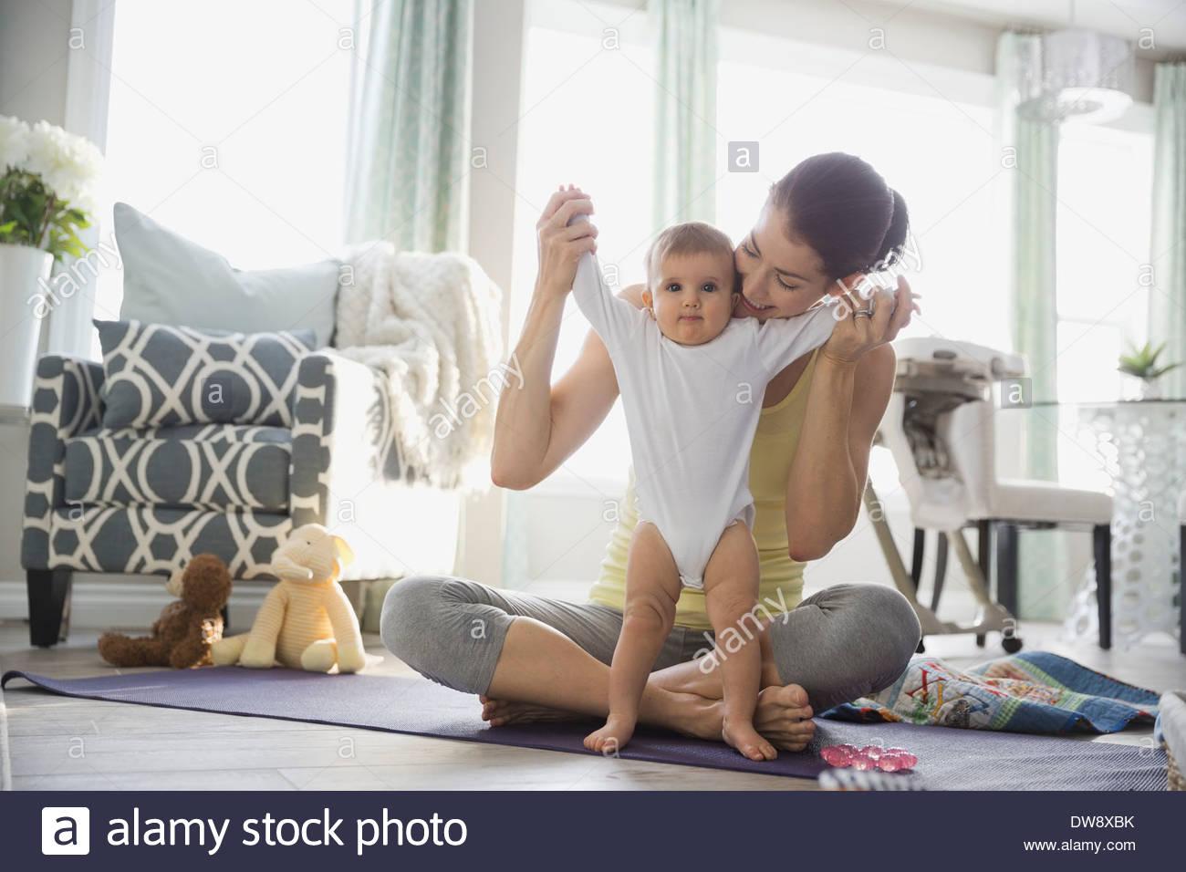Mutter mit Babymädchen spielen auf Yoga-Matte Stockbild