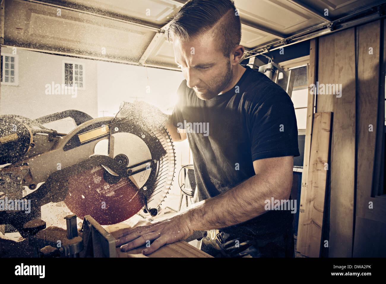 Männliche Schreiner Sägen Holzbrett in Werkstatt Stockbild