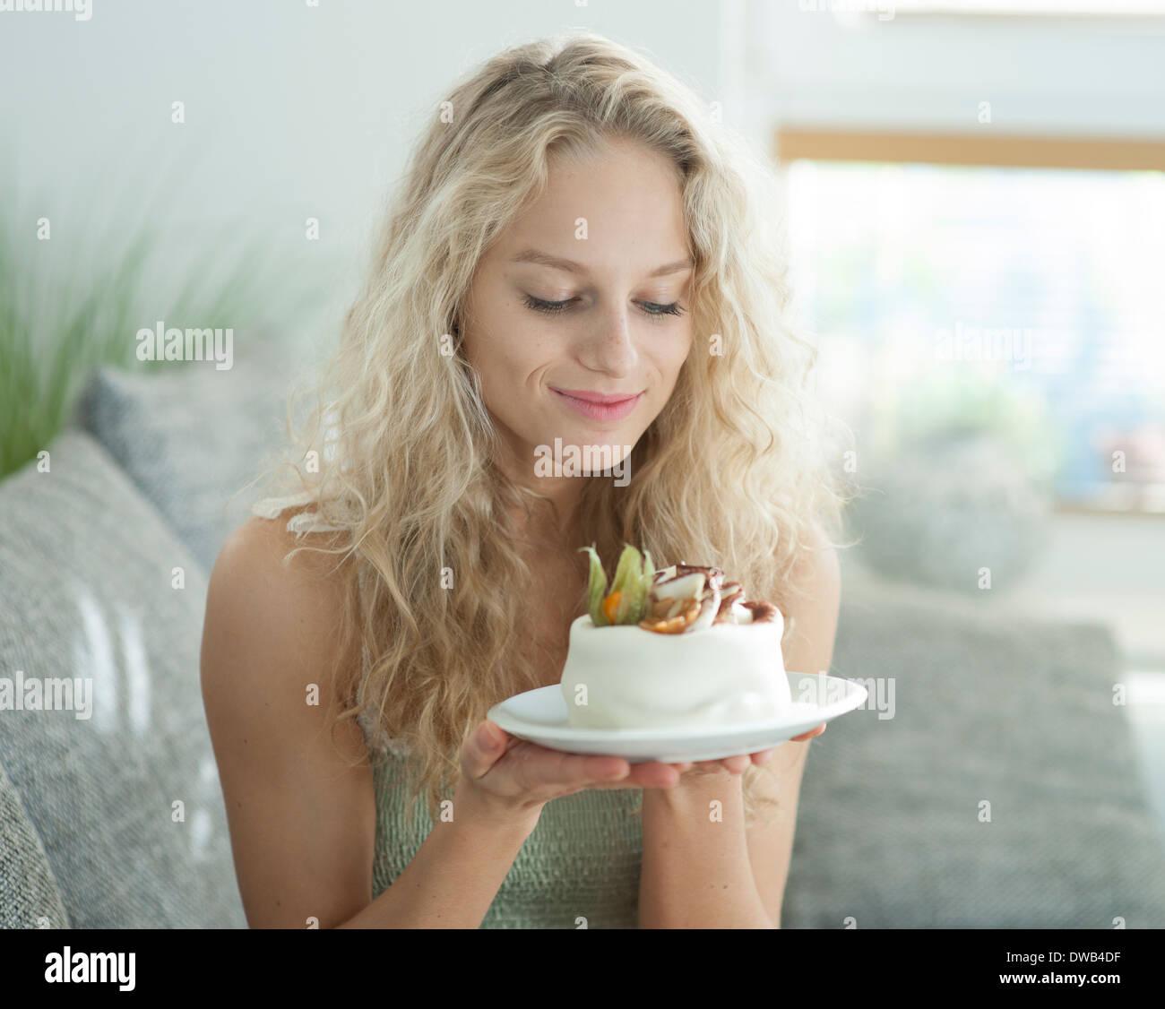 Schöne junge Frau, die verlockenden Kuchen im Haus zu betrachten Stockbild