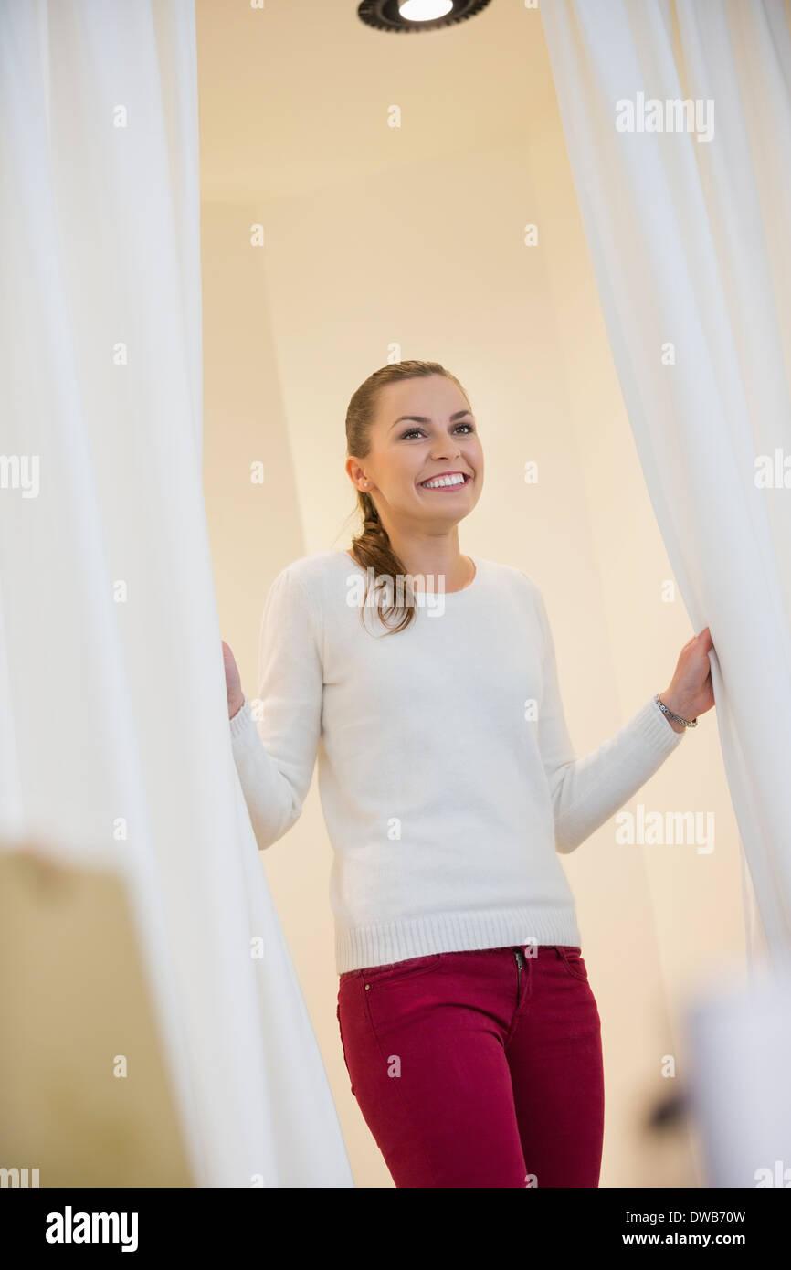 Glückliche Frau in Umkleidekabine Vorhänge öffnen Stockbild