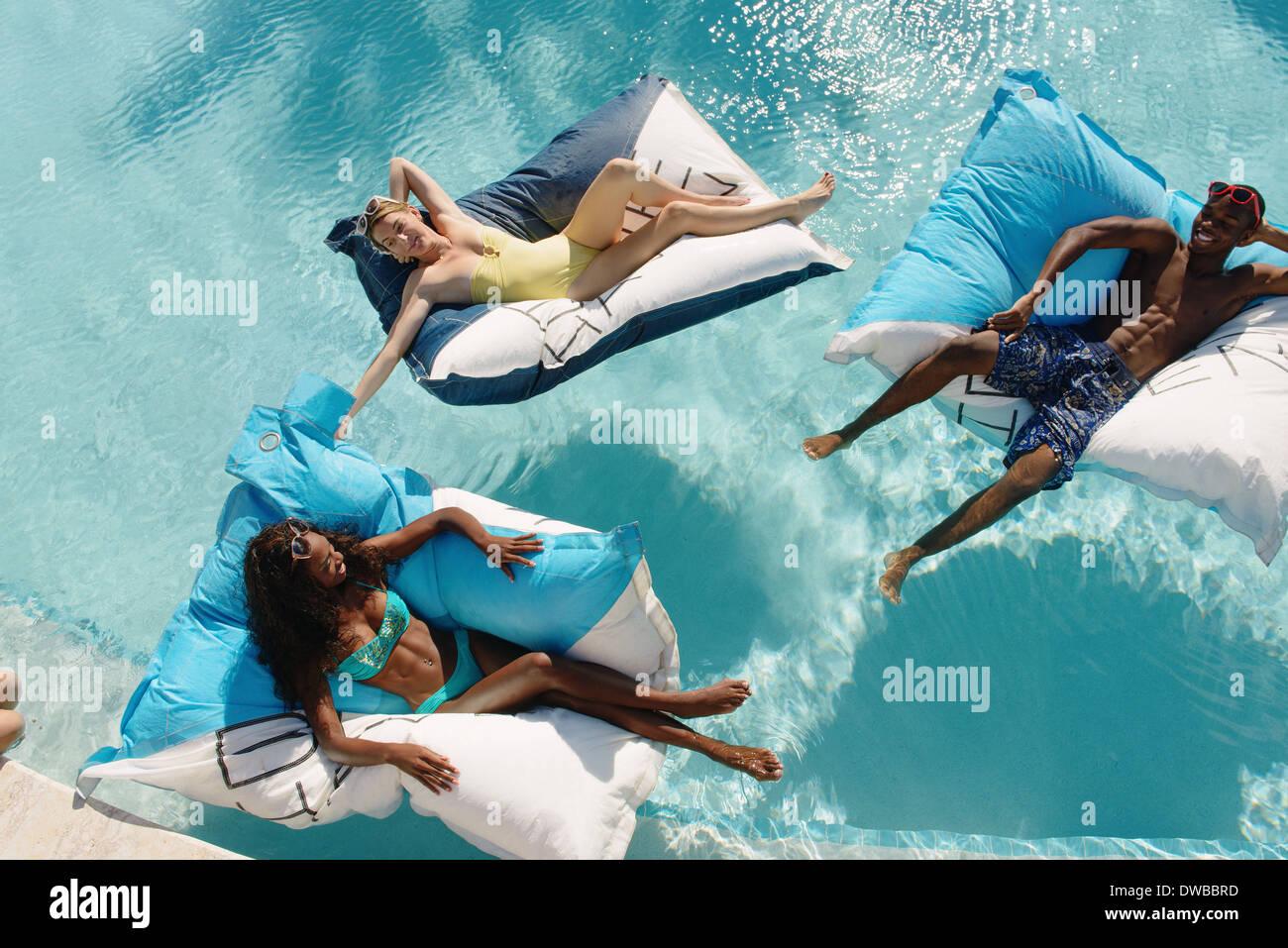 Drei junge Erwachsene liegen auf Luftmatratzen im Schwimmbad, Providenciales, Turks-und Caicosinseln, Caribbean Stockbild
