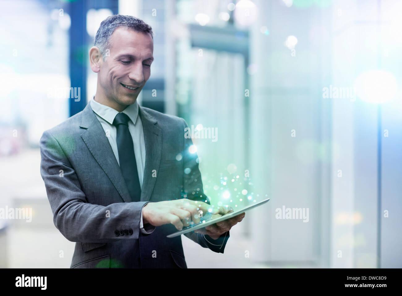 Geschäftsmann mit digital-Tablette mit leuchtenden Lichter kommen aus ihm heraus Stockbild