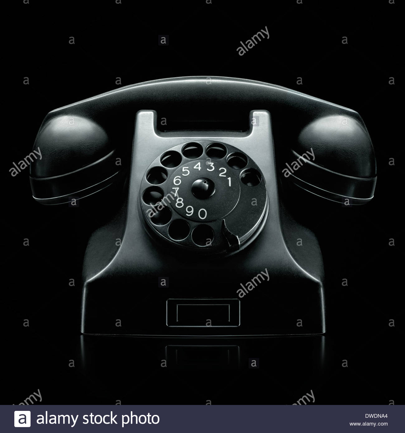 alte Vintage schwarze Wählscheibe Telefon auf sehr launisch dunklen schwarzen Hintergrund fotografiert Stockbild
