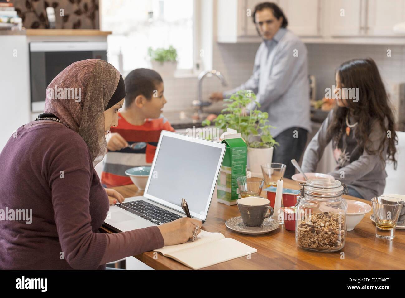Muslimische Küche | Die Muslimische Frau Die Arbeiten Am Laptop Mit Der Familie