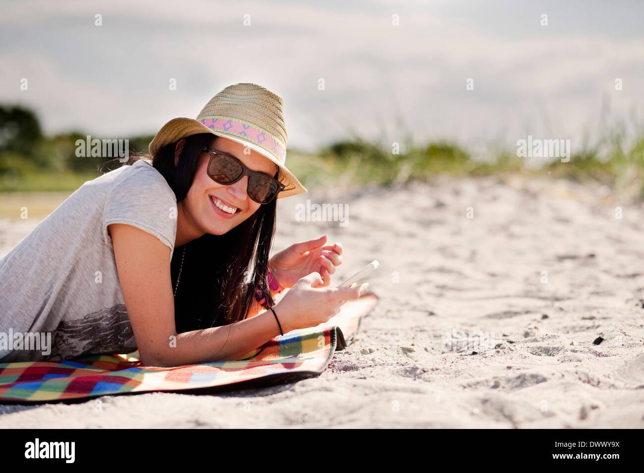 Porträt der glückliche Frau halten Handys beim liegen auf der Picknickdecke Stockbild