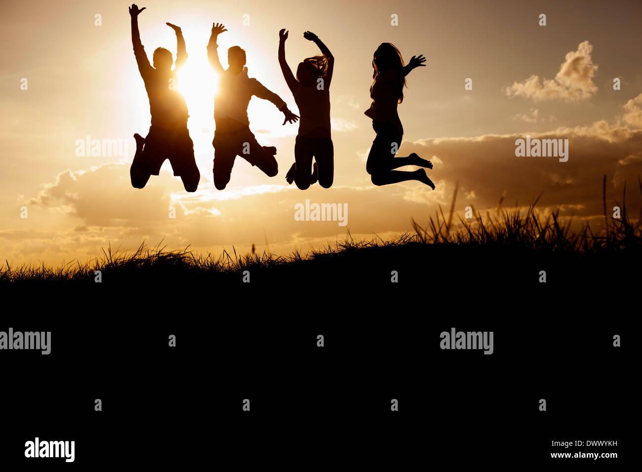 Silhouette Bild von Freunden am Strand gegen Himmel springen Stockbild