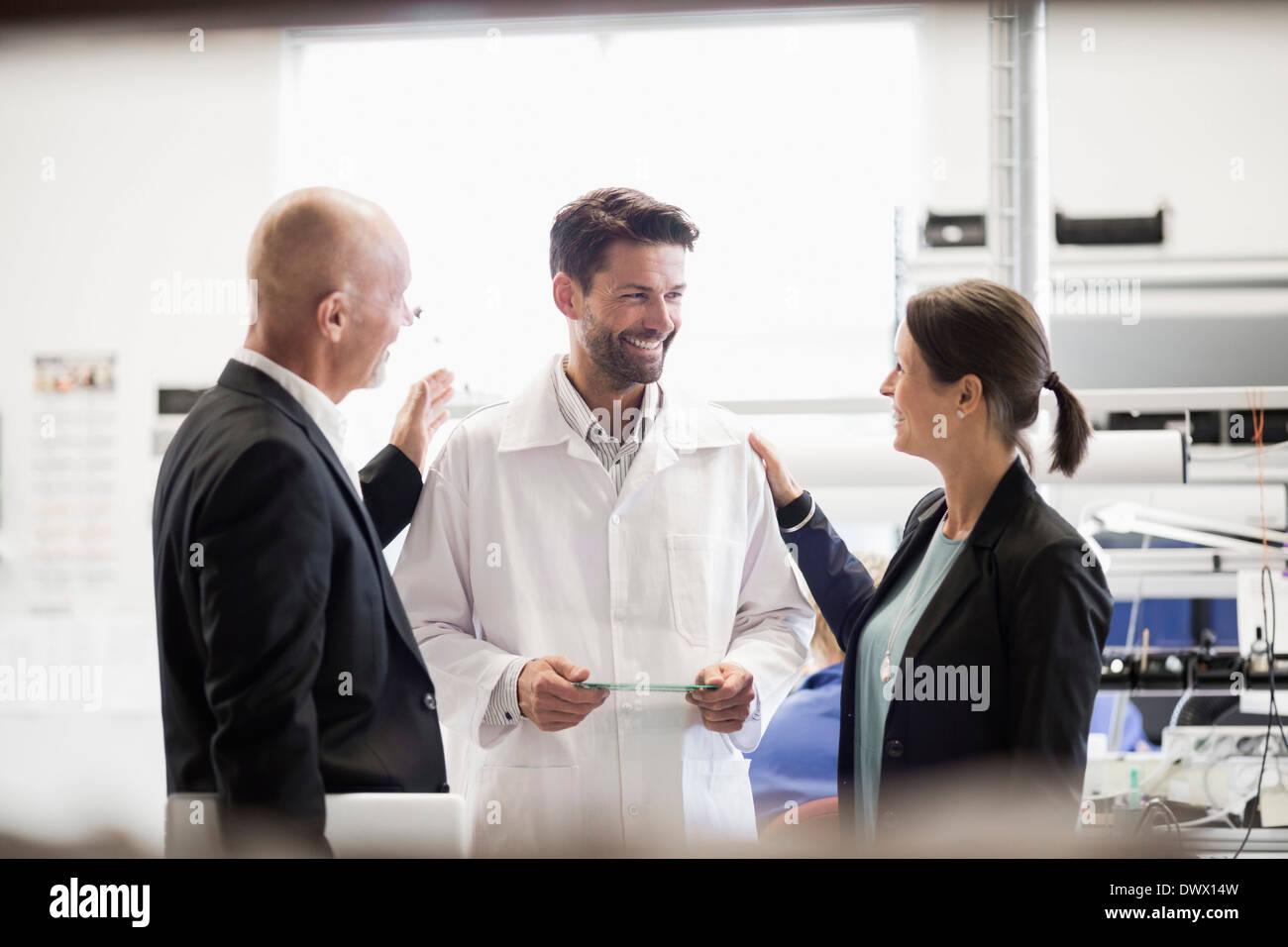 Glücklich Geschäftsleute und Ingenieur mit Platine in der Industrie Stockbild