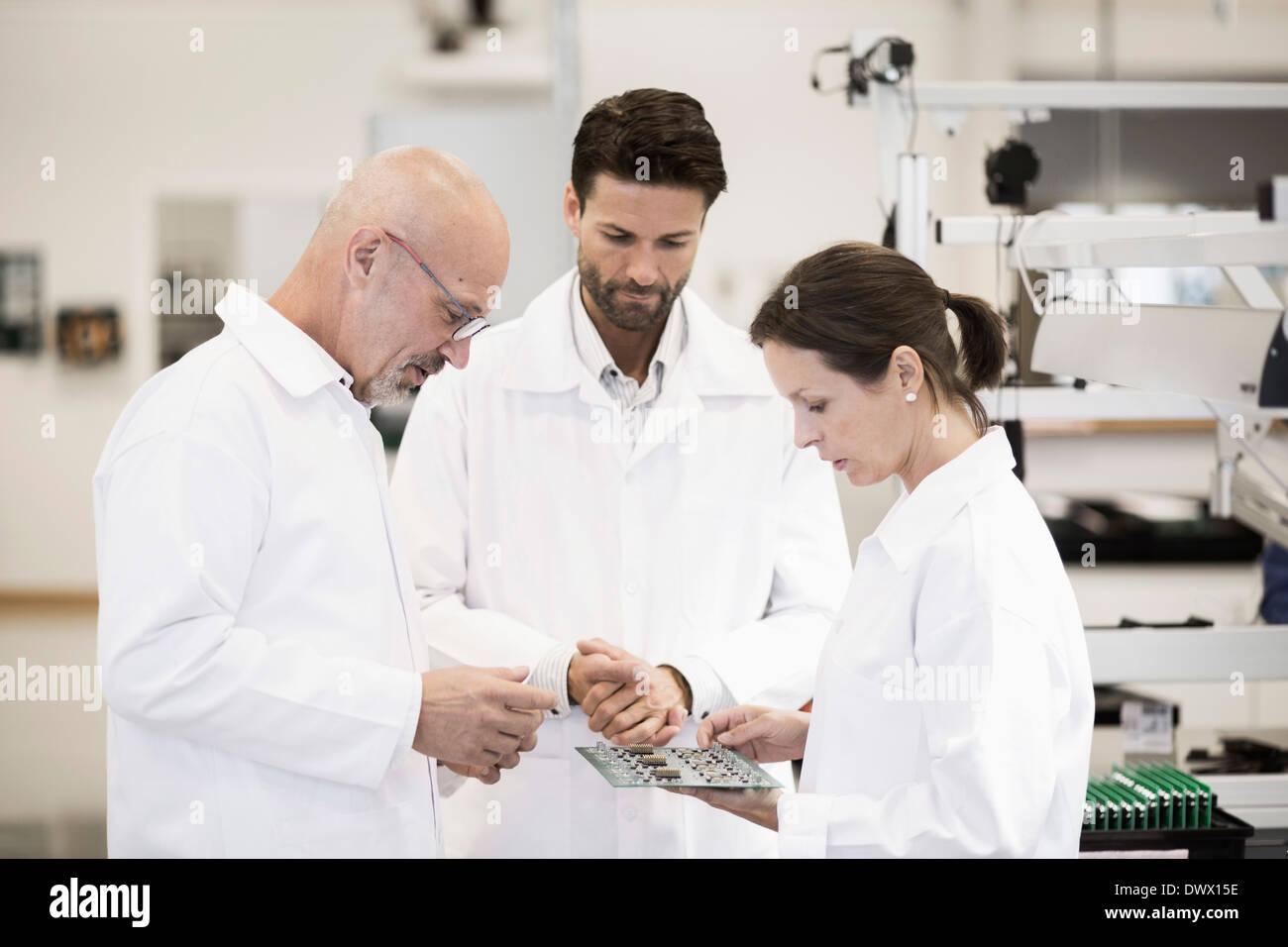 Team von Technikern, die Platine im Werk zu prüfen Stockbild
