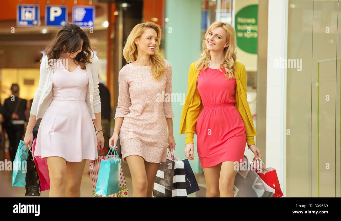 Drei attraktive Frauen zu Fuß durch das Einkaufszentrum Stockbild