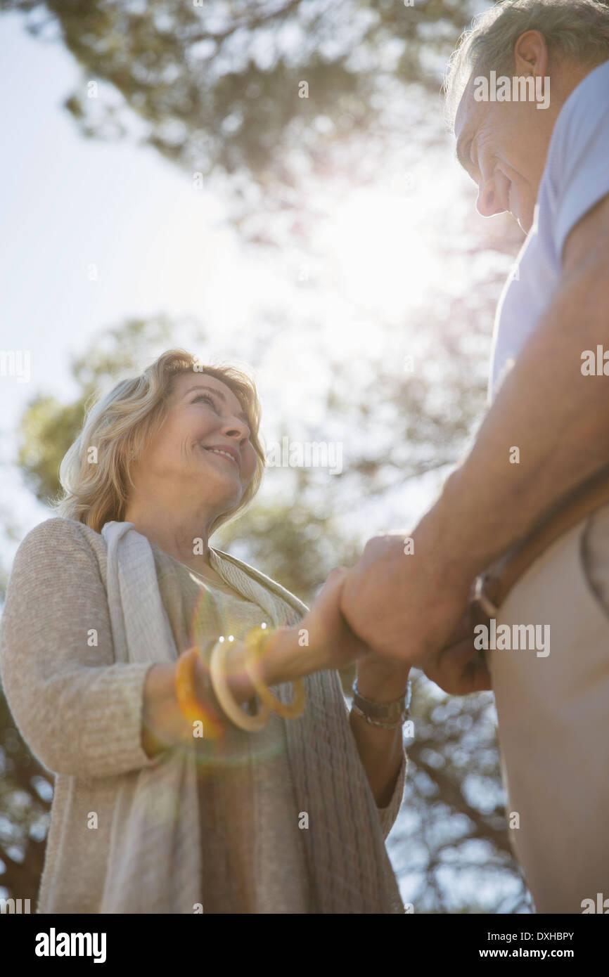 Älteres Paar Hand in Hand unter Bäumen Stockbild