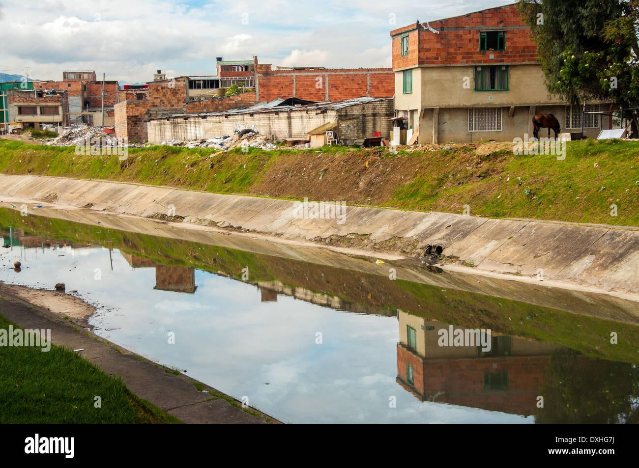 Eine niedrigeren Klasse Nachbarschaft spiegelt sich in einem Fluss in Bogota, Kolumbien Stockbild