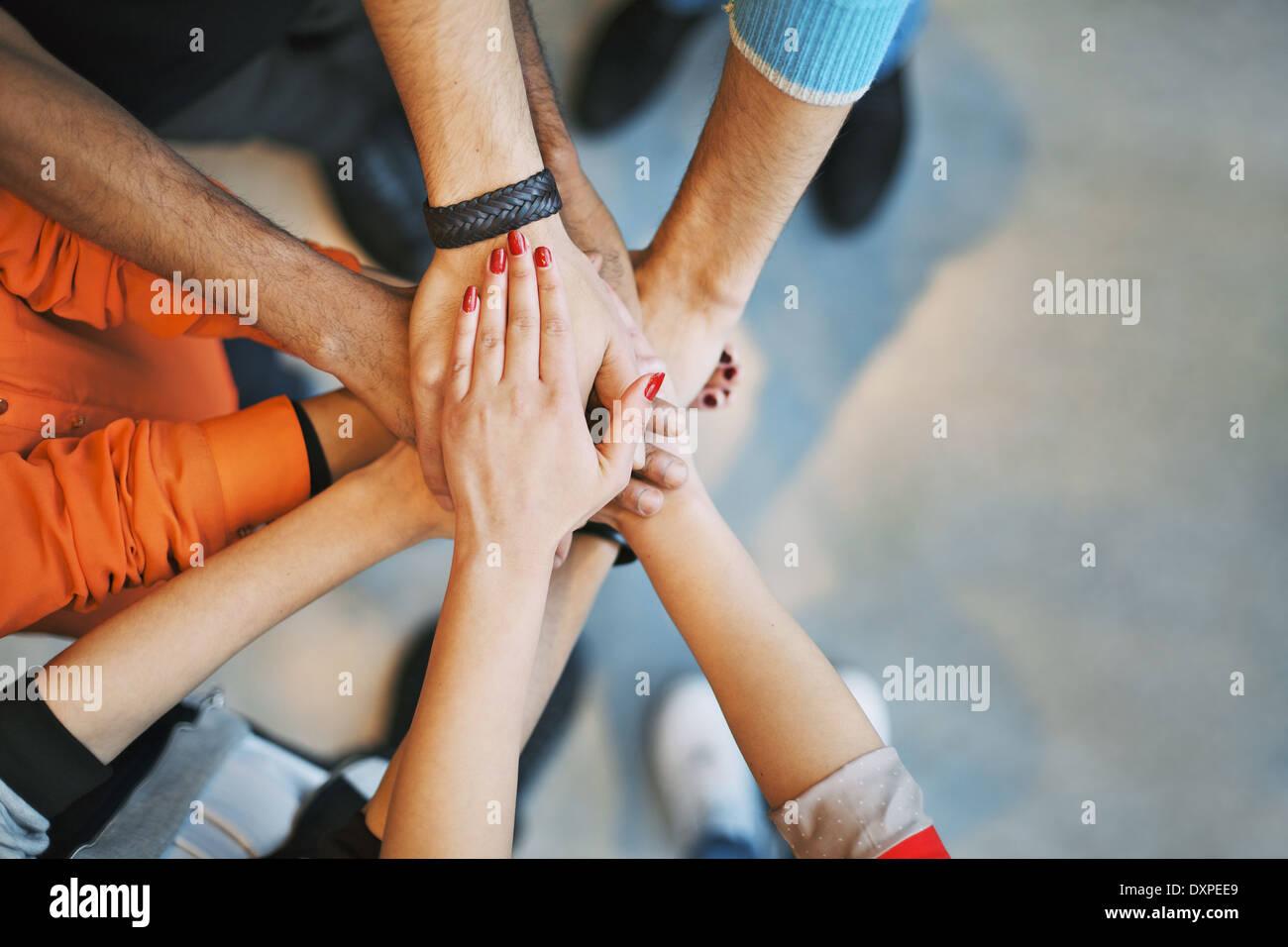 Multiethnische Gruppe von jungen Leuten, die ihre Hände übereinander. Schließen Sie herauf Bild der Stockbild