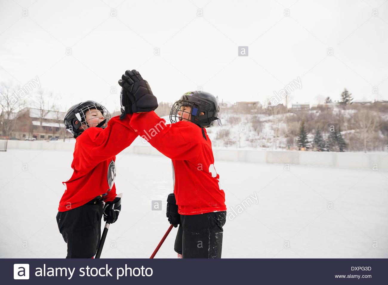 Eishockey-Spieler geben High-Five auf Eisbahn Stockbild