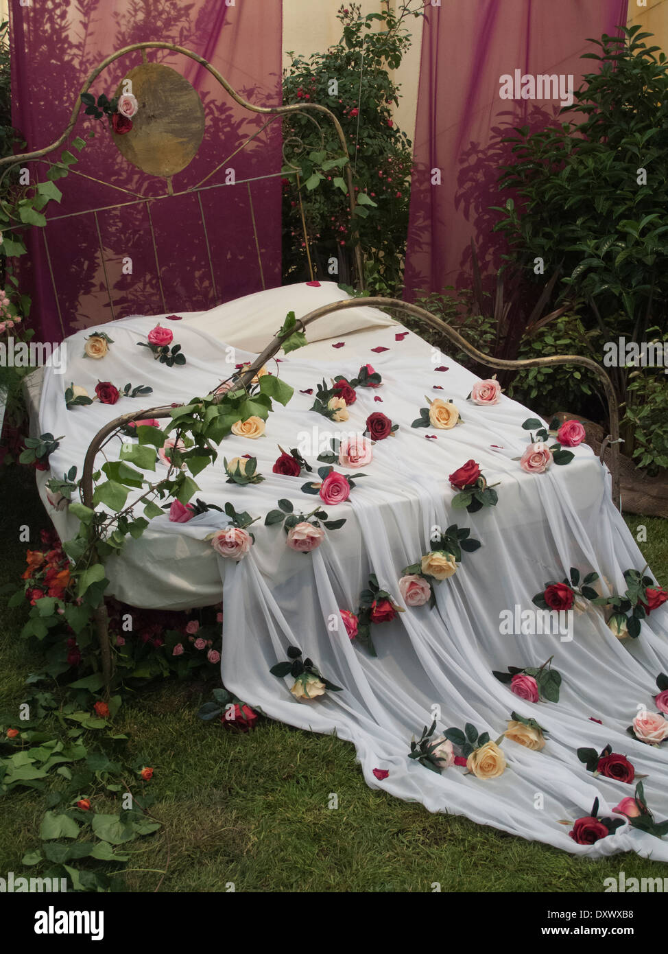 Bett im romantischen Stil mit Bettwäsche und Rosenblätter in Ausstellung Display, Spanien Stockbild