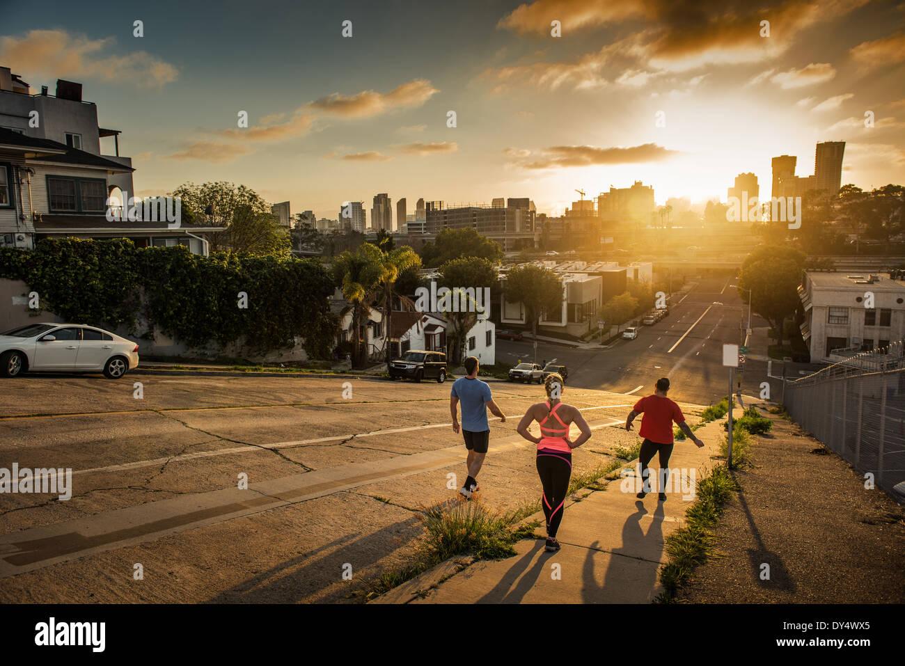 Team der Läufer einen steilen Stadt Hügel hinunter laufen Stockbild