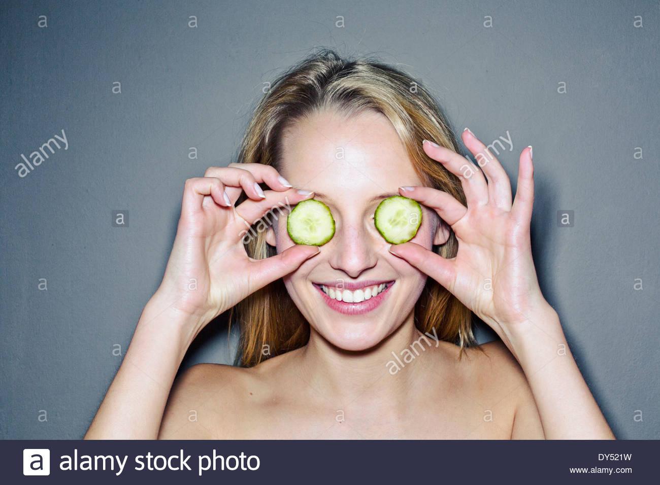 Junge Frau mit Gurkenscheiben Augen bedecken Stockbild