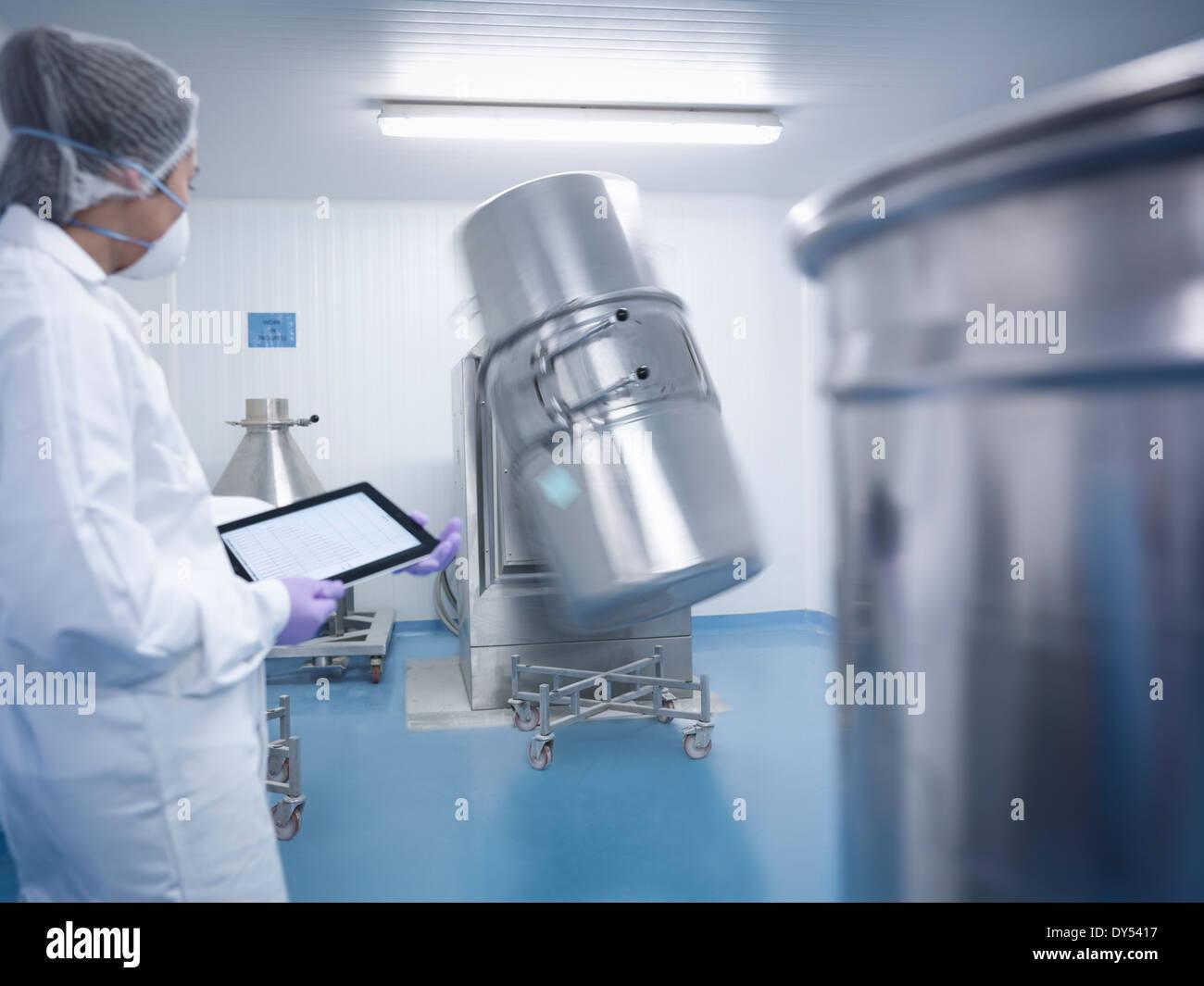 Arbeiter halten digital-Tablette und beobachtete Zutat Mischmaschine in pharmazeutische Fabrik Stockbild