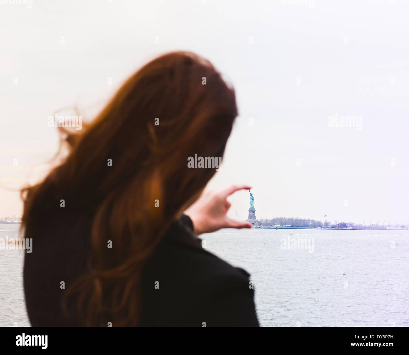 Junge Frau ausrichten Finger mit der Freiheitsstatue, New York, USA Stockbild