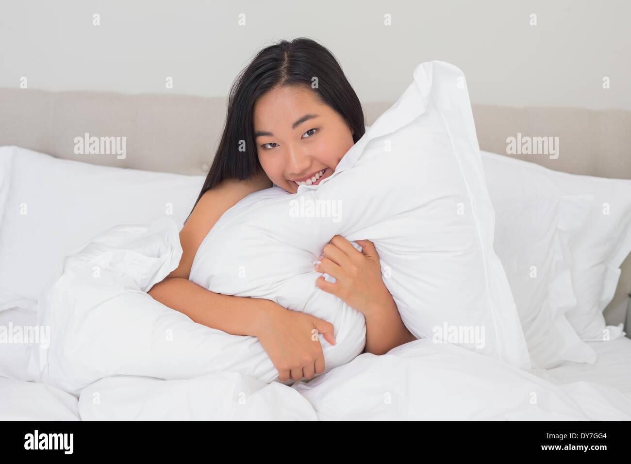 Lächelnde Frau umarmt ihr Kissen Stockbild
