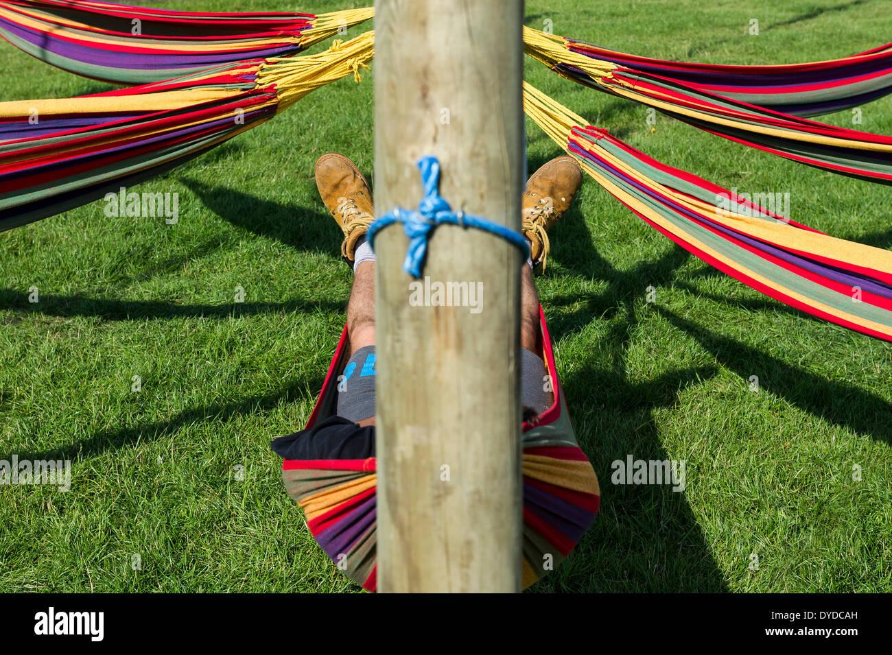 Ein Mann schlafen in einer Hängematte auf dem Brownstock Festival in Essex. Stockbild