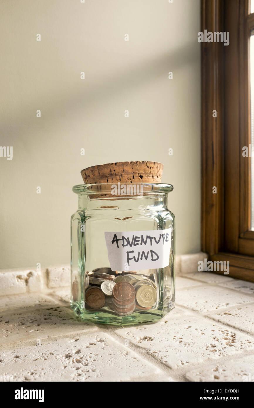 Glas gekennzeichnet Abenteuer Fonds mit Kleingeld. Stockbild