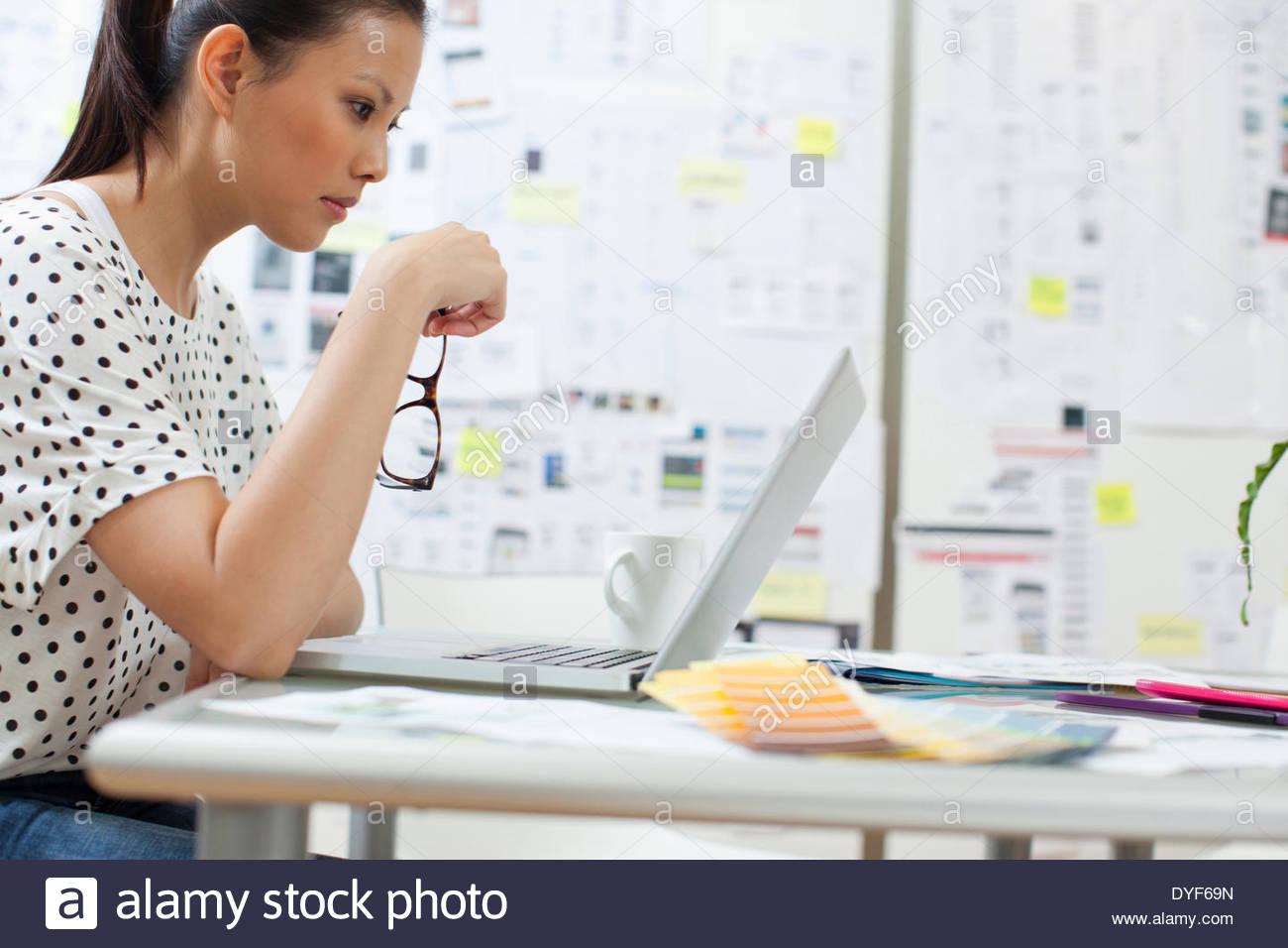 Ernsthafte Geschäftsfrau auf der Suche nach Laptop im Büro Stockbild