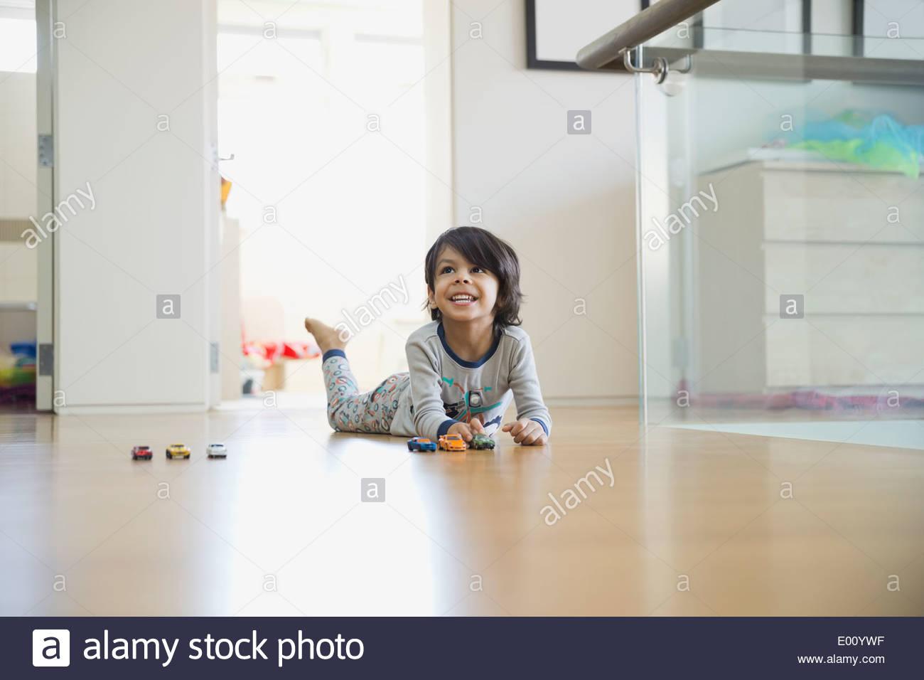 Jungen spielen mit Spielzeugautos auf Etage Stockbild