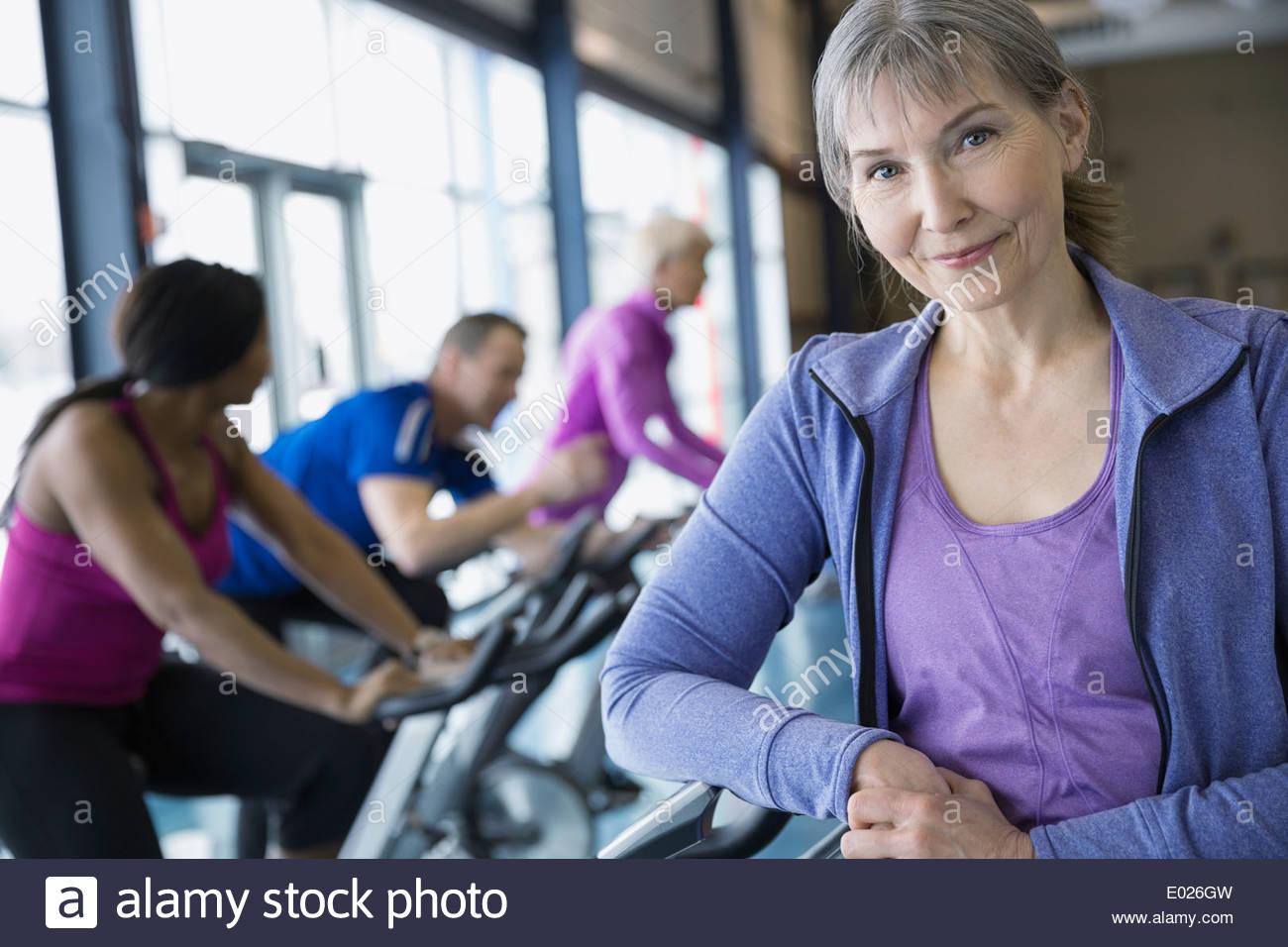 Porträt der lächelnde Frau stützte sich auf Heimtrainer Stockbild