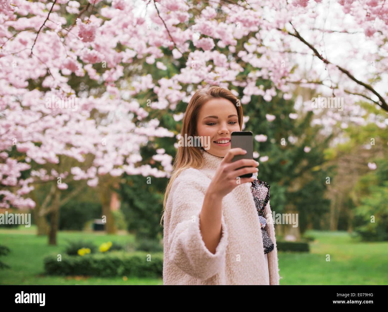 Schöne junge Frau fotografieren mit Smartphone im Frühjahr blühen Park. Kaukasischen Frauen schießen Stockbild