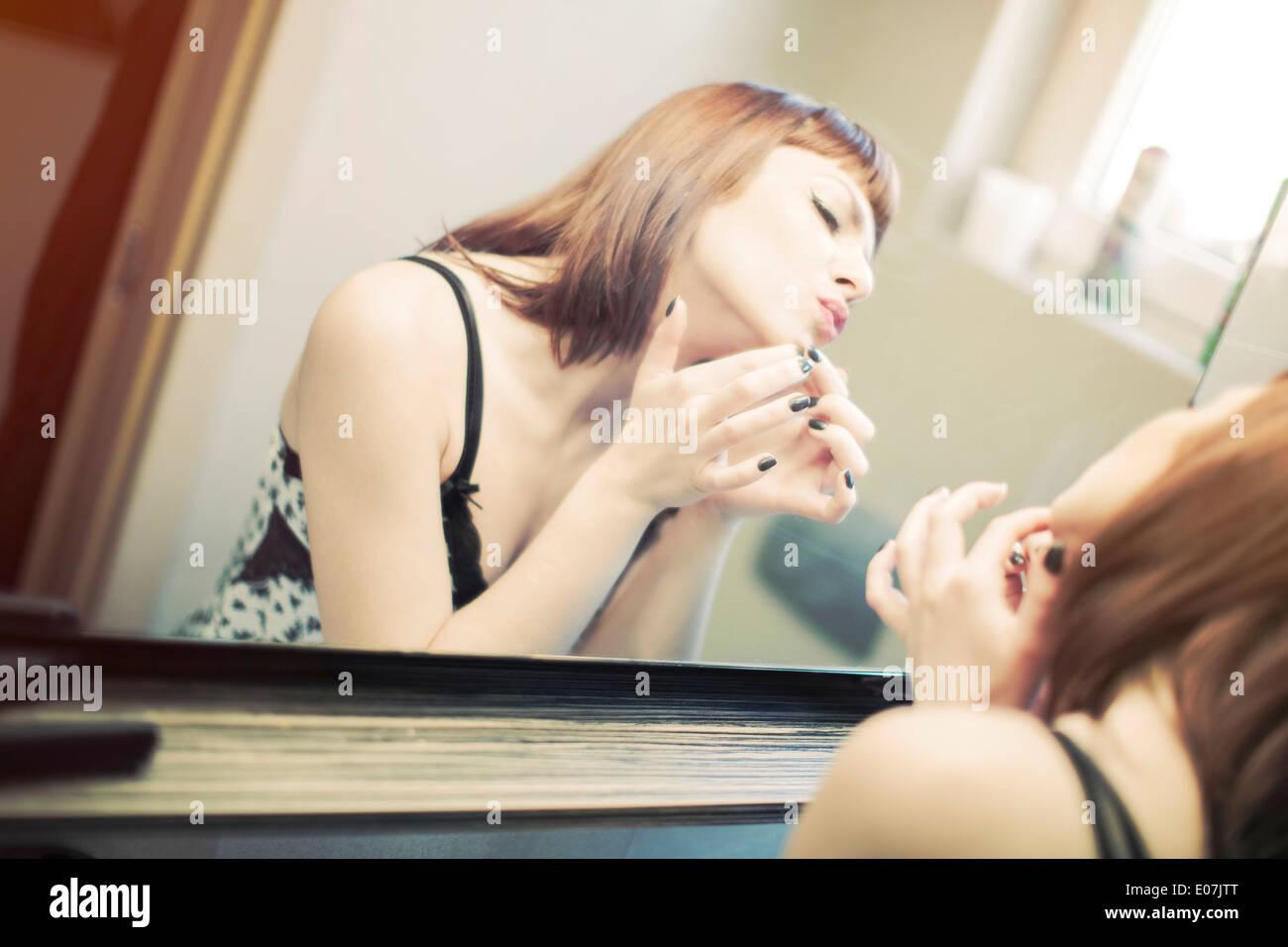 Junge Frau im Nachthemd vor einem Spiegel Stockbild