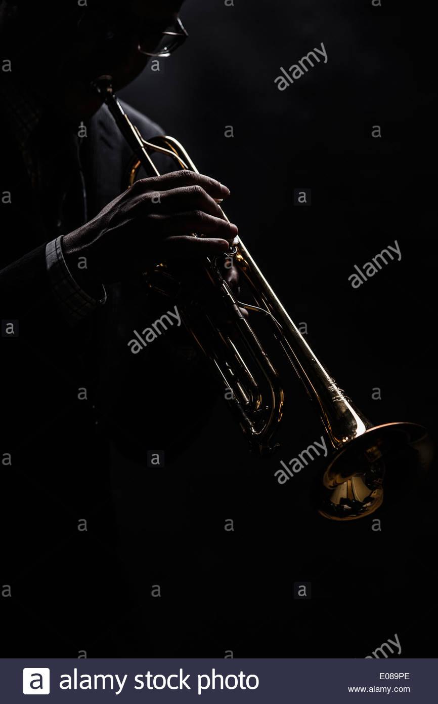 Musiker, spielt Trompete auf schwarzem Hintergrund Stockbild
